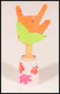 picture of a construction paper flower made from a hand with the 2 middle fingers glued down to sign I LOVE YOU. The flower is on a craft stick stem and the sten is stuck into the top of a paper cup for a flowerpot.